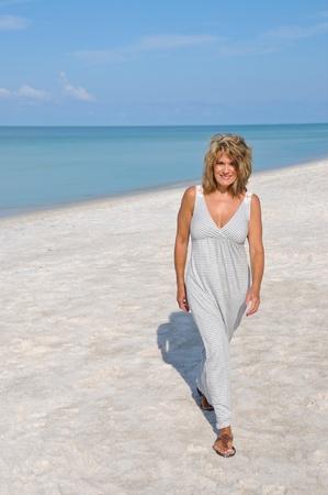 donne mature sexy: Donna attraente a piedi sulla spiaggia in un Sundress Archivio Fotografico