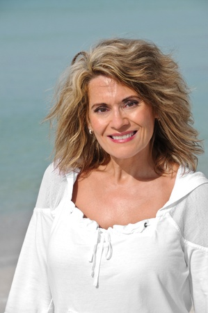 40 50: Outdoor Portrait of an Attractive Middle Age Woman Wearing White Top  Stock Photo
