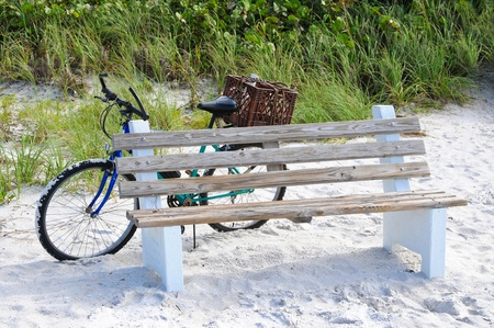 Bicycle Leaning against a Wooden Bench on the Beach photo