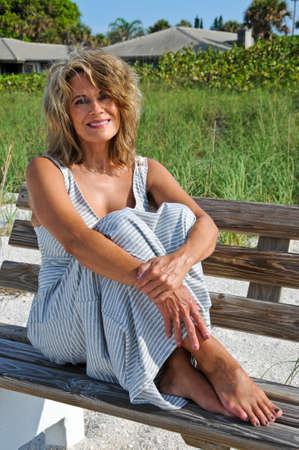 donne mature sexy: Donna attraente seduta su una panchina in spiaggia Archivio Fotografico