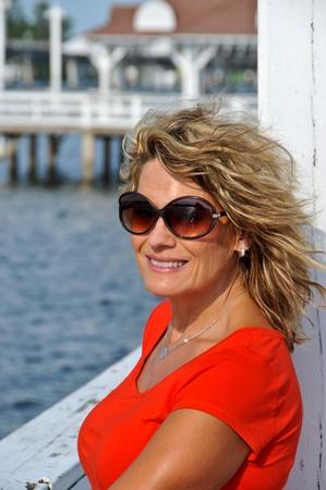 donne mature sexy: Attraente sorridente donna di mezza et� che porta Red Top Appoggiato corrimano con mare sullo sfondo