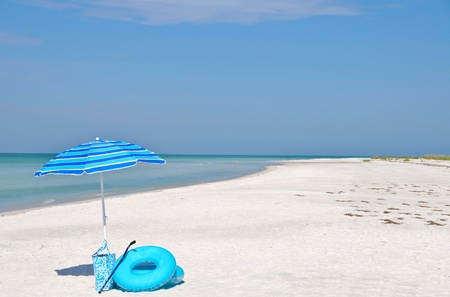 floats: Blue Striped Beach Umbrella, Floats and Beach Bag on the coastline of Florida Stock Photo