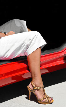 get out: Womans leg in high heel shoes getting out of a car
