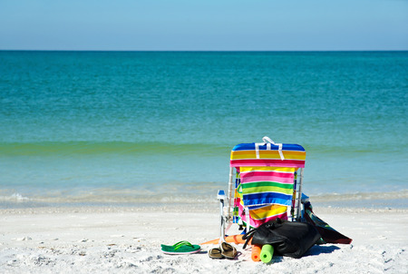 floats: Bright Color Beach Chair with flip flops, floats and bag on the Beach