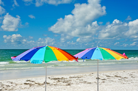 Two Multi-Colored Beach Umbrellas against the Ocean and Sky photo