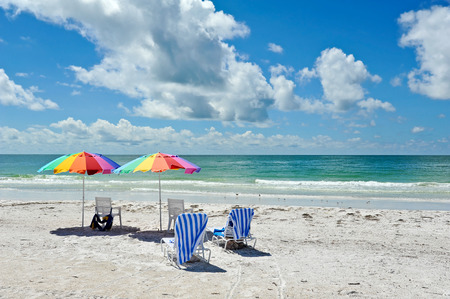 florida beach: Two Beach Chairs with Colorful Umbrellas on the Beach Stock Photo