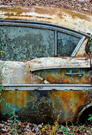 junkyard: An old rusted out scrap car that has been abandoned in the woods