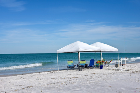 provide: Two Portable Canopys with Lounge Chairs set up to provide shade on the Beach Stock Photo