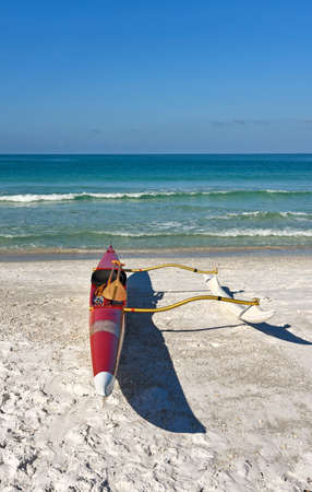 outrigger: An outrigger canoe sitting on a white sandy beach with ocean in the background Stock Photo