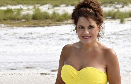 Outdoor Portrait of a Beautiful Mature Woman on the beach wearing a yellow top.