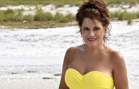 belle brunette: Portrait ext�rieure d'une belle femme d'�ge m�r sur la plage v�tue d'un haut jaune.
