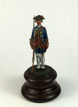 plumb: one plumb toy soldier on a  brown wood base Stock Photo