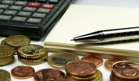 plusieurs pièces en euros bloc-notes et stylo calculatrice