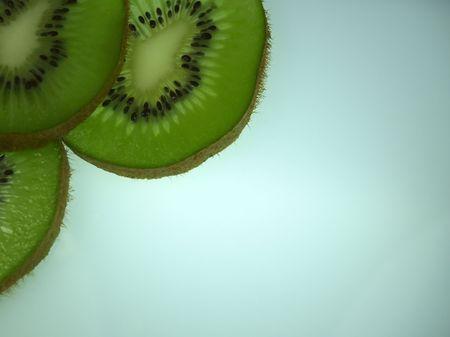 trois tranches de kiwi sur un dessus de bureau blanc