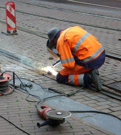 travailleur avec masque de protection et des gants de soudage train ferroviaire et sparks propagation