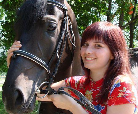 caballo negro: Modelo joven del brunette con el caballo negro debajo del �rbol 06 del rowan Foto de archivo