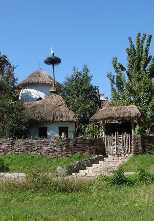 nonviolent: Peaceful Ancient Ukrainian Yard in Summer Village with Stork Nest Stock Photo