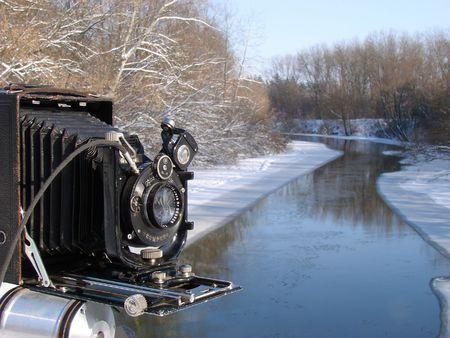 Ancient photo camera shoting snowy morning riverside Stock Photo - 736805