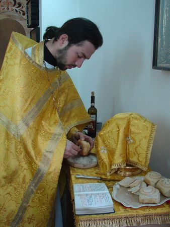 Russian Orthodox priest preparing Sacred Participle foods photo