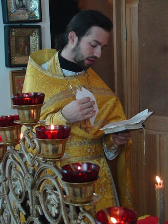 Russian Orthodox priest reading Holy Gospel photo