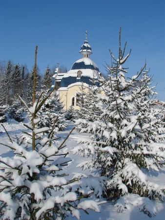 Winter snowy landscape with fur-trees and church photo