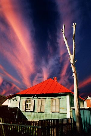 obliteration: Abandoned green wooden house with red roof opon dramatic sky Stock Photo