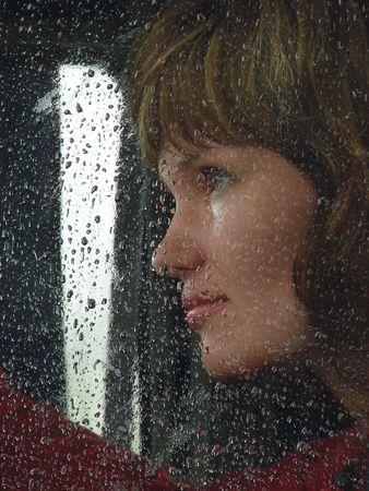 Girl looks thru waterdropped widow glass in rainy weather photo