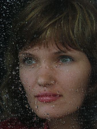 Girl looks thru waterdropped widow glass in rainy weather photo