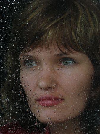 Girl looks thru waterdropped widow glass in rainy weather