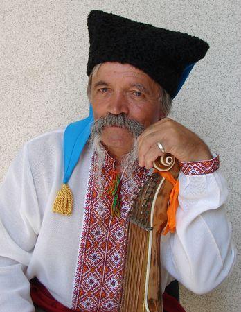 Senior ukrainian folk travelling musician bandurist named Kobzar with instrument bandura photo