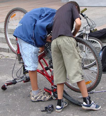 bycicle: Two street boys mending new bycicle Stock Photo