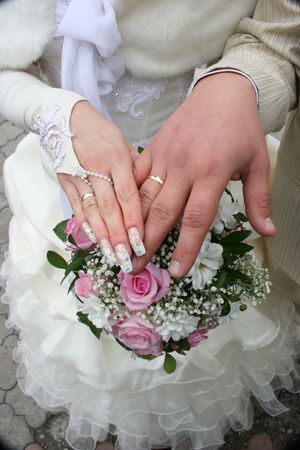 Female and male hands of newlyweds with bouquete Stock Photo - 1767948