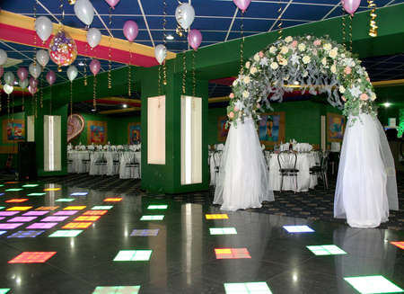 artificial lights: Wedding party hall decoration with white veil arc Stock Photo