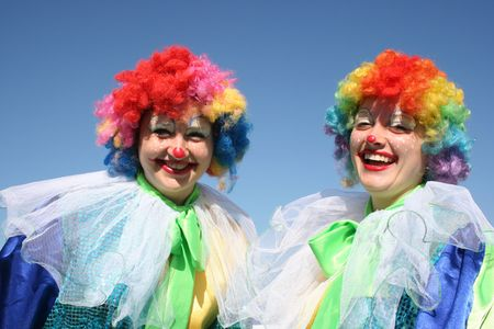 Two bizzare clowns in colored wigs upon blue sky 4