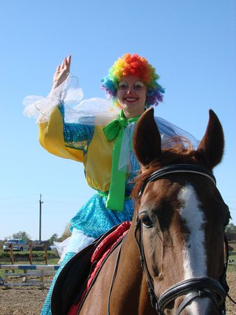 Equestrian expressive clown in colored wig upon blue sky 1 photo