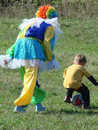 Clown in colored wig playing with a boy photo
