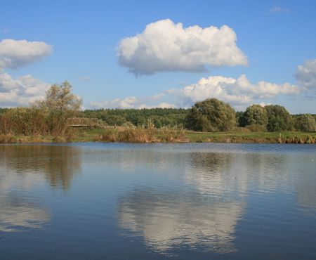 Cloudy deep ue sky over yellow autumn forest and pond photo