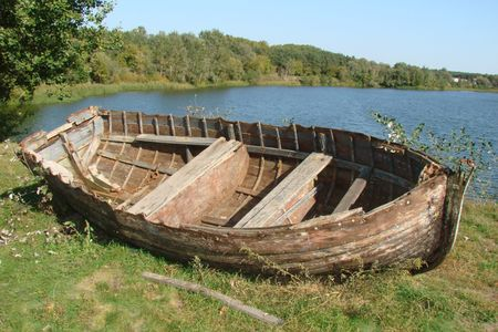 ruined vintage wooden boat on riverside photo