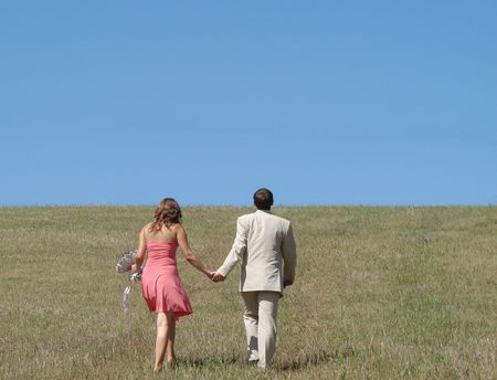 Young couple walking in wide green field under blue sky photo