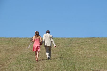 accompanied: Young couple walking in wide green field under blue sky Stock Photo