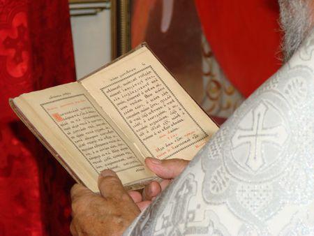 Slavic Gospel in hands of russian orthodox priest photo
