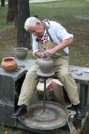 craftwork: Old potter working with clay on wheel