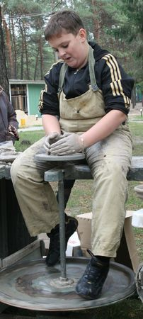 Young boy potter working with clay on wheel photo