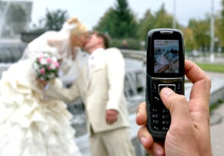 Newlyweds kissing behind cameraphone shooter photo