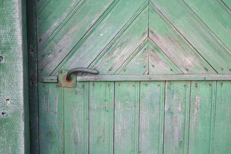 Aged door handle on green wooden entrance door photo