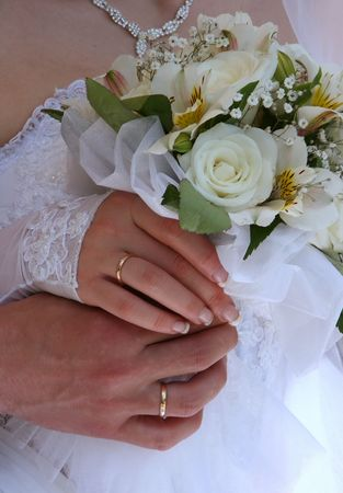Female and male hands of newlyweds with bouquet Stock Photo - 3312893
