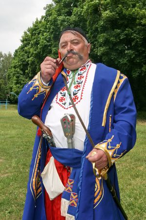 Old ukrainian Cossack with long whiskers smoking pipe