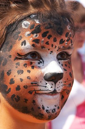 tanned girl: cute girl kid face with painted panther color mask Stock Photo