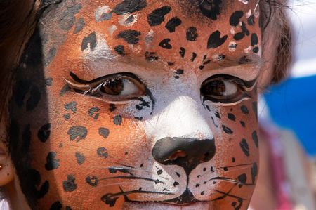 cute girl kid face with painted panther color mask Stock Photo