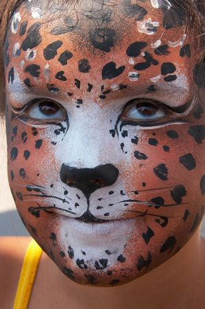 cute girl kid face with painted panther color mask photo